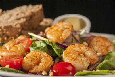 Salade met Scampi's met rode ui, tomaat, pijnboompitjes en dressing